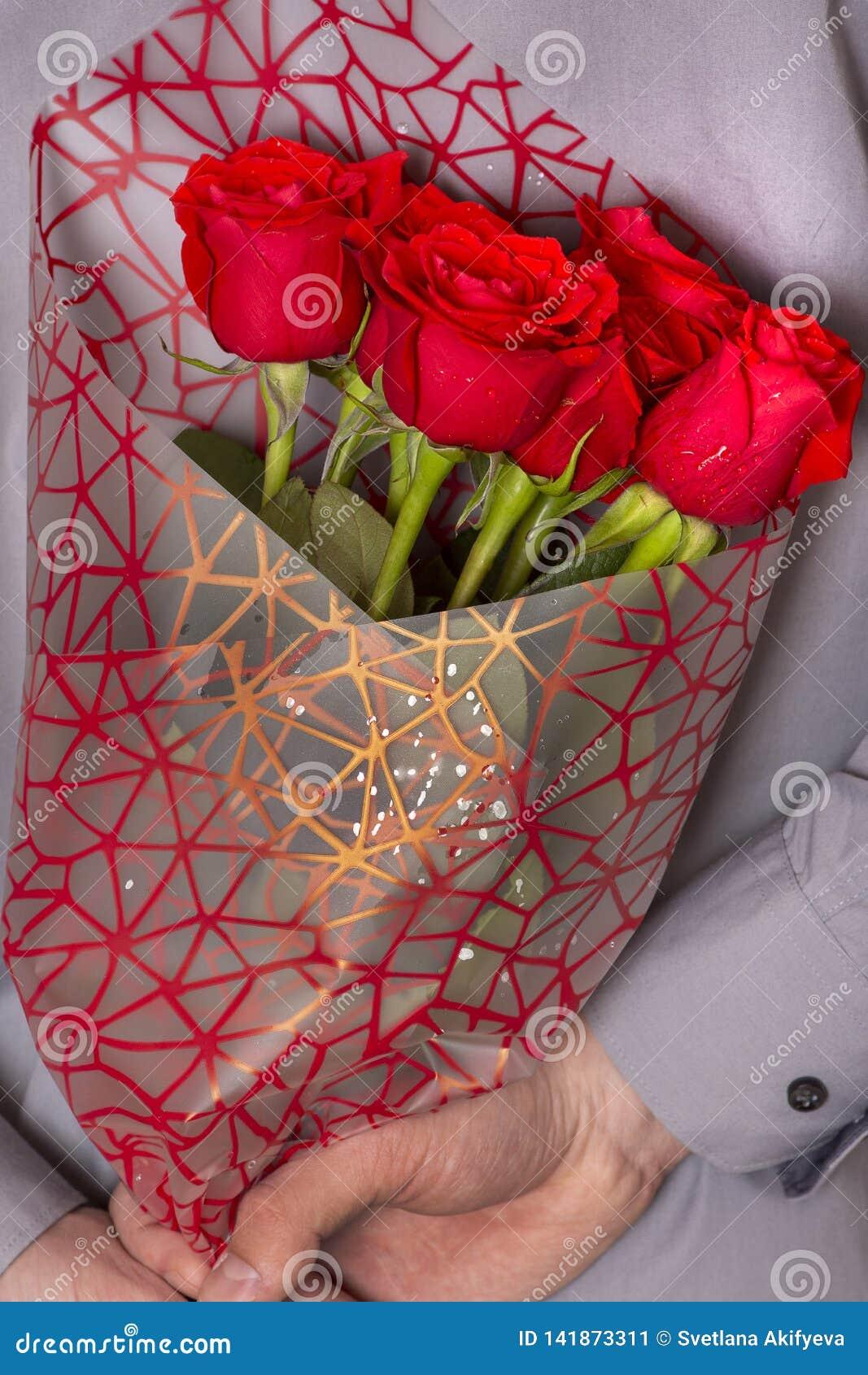 Ein Mann, der einen Blumenstrauß von roten Rosen hält