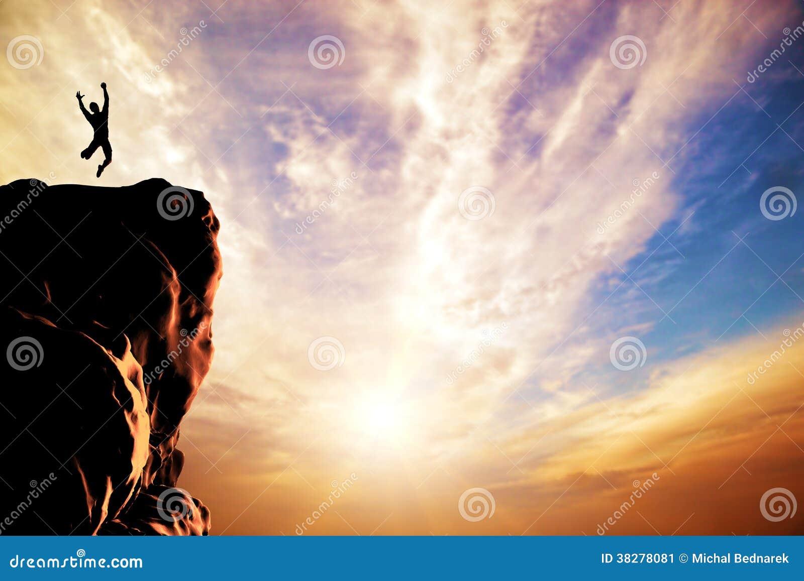 Ein Mann, der für Freude auf der Spitze des Berges springt
