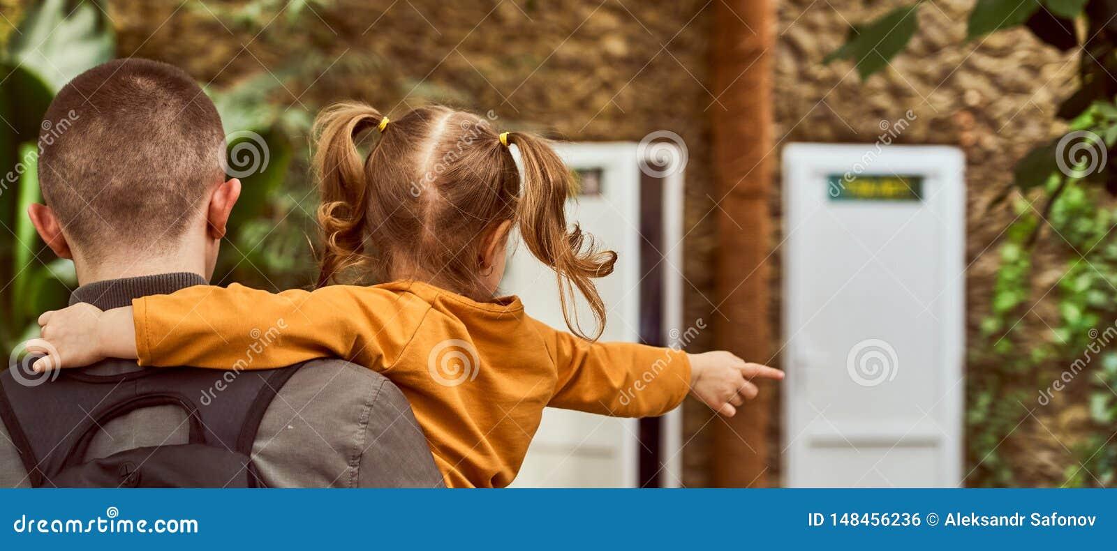 Ein Mann, der ein Kind in seinen Armen, Rückseite im Rahmen hält, gehen