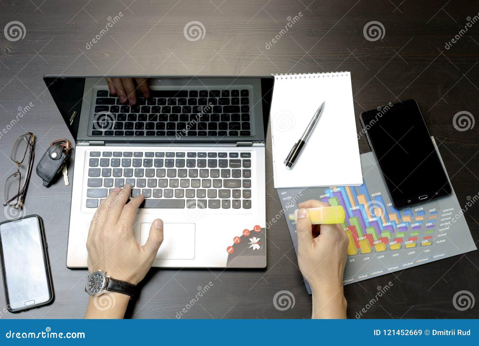 Ein Mann druckt auf einem Laptop und liegt nahe bei dem Telefon, Tablette glasse