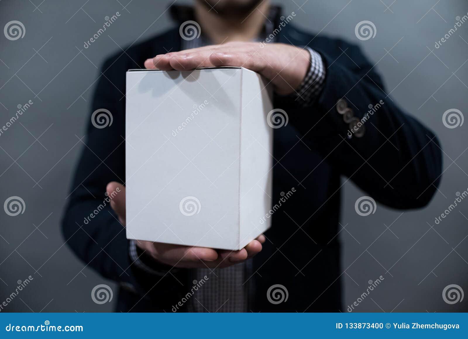 Ein Mann in einer Jacke und in einem Hemd, die einen Weißbuchkasten halten