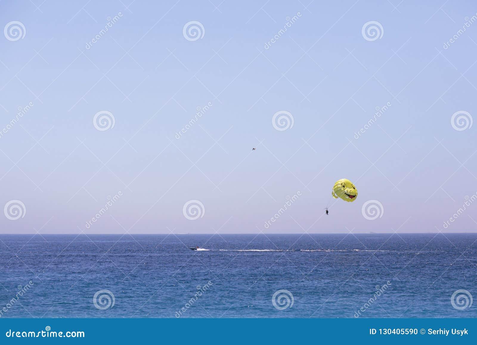 Ein Mann fliegt auf einen Fallschirm für ein Boot Parasailing