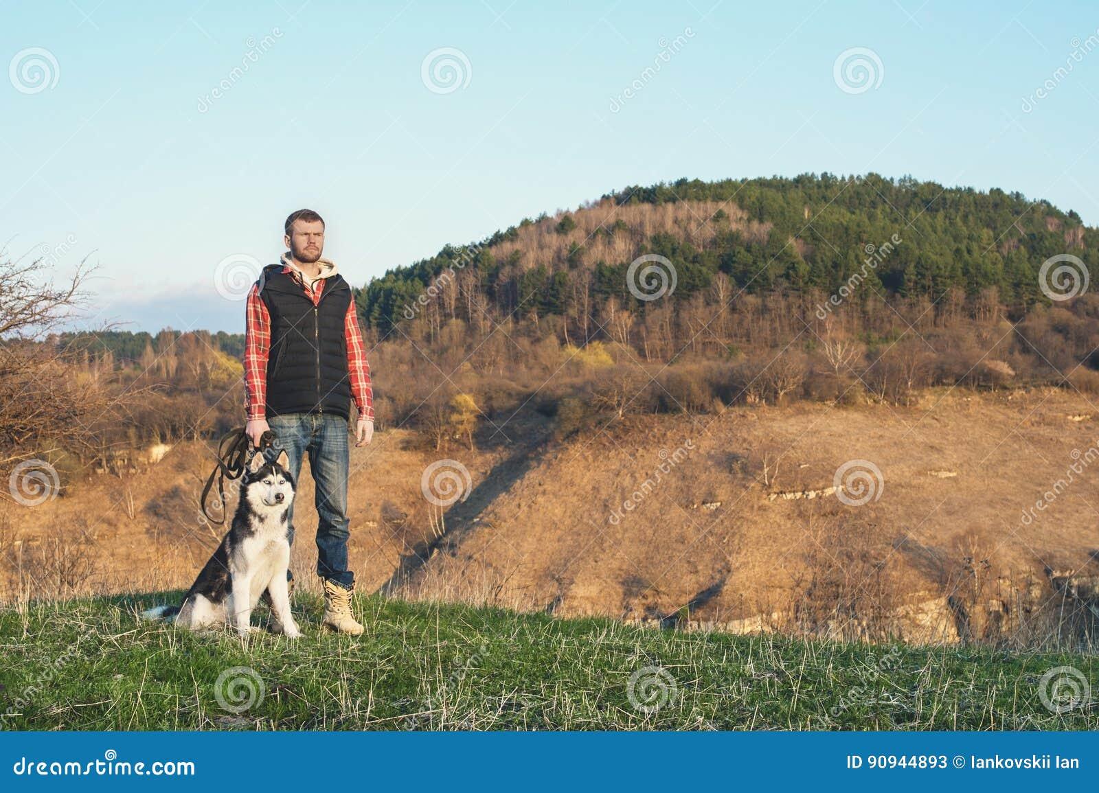 ein mann mit einem bart gehend sein hund in der natur stehend mit einer hintergrundbeleuchtung. Black Bedroom Furniture Sets. Home Design Ideas
