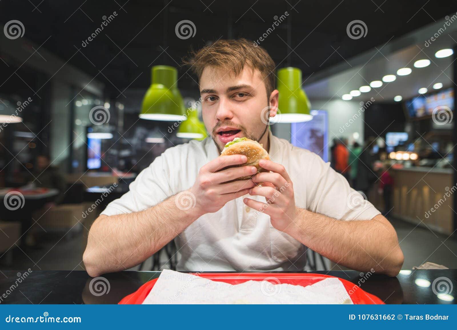 Ein Mann mit einem Bart sitzt in einem Schnellrestaurant mit einem Burger in seinen Händen und betrachtet die Kamera