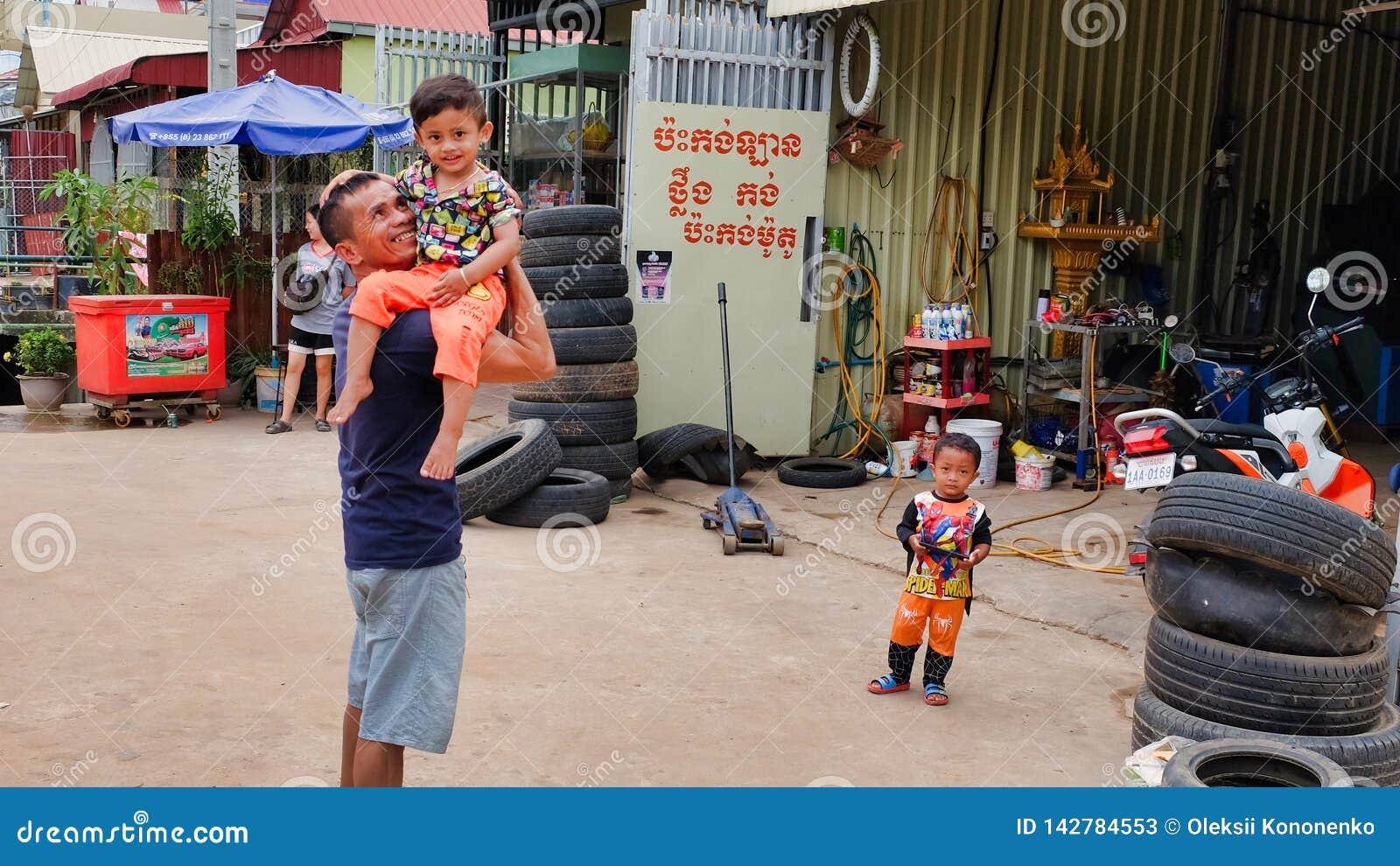 Ein Mann mit einem Kind in seinen Armen nahe dem Reifengeschäft, Elendsviertel von Asien, Bewohner von schlechten Bereichen von