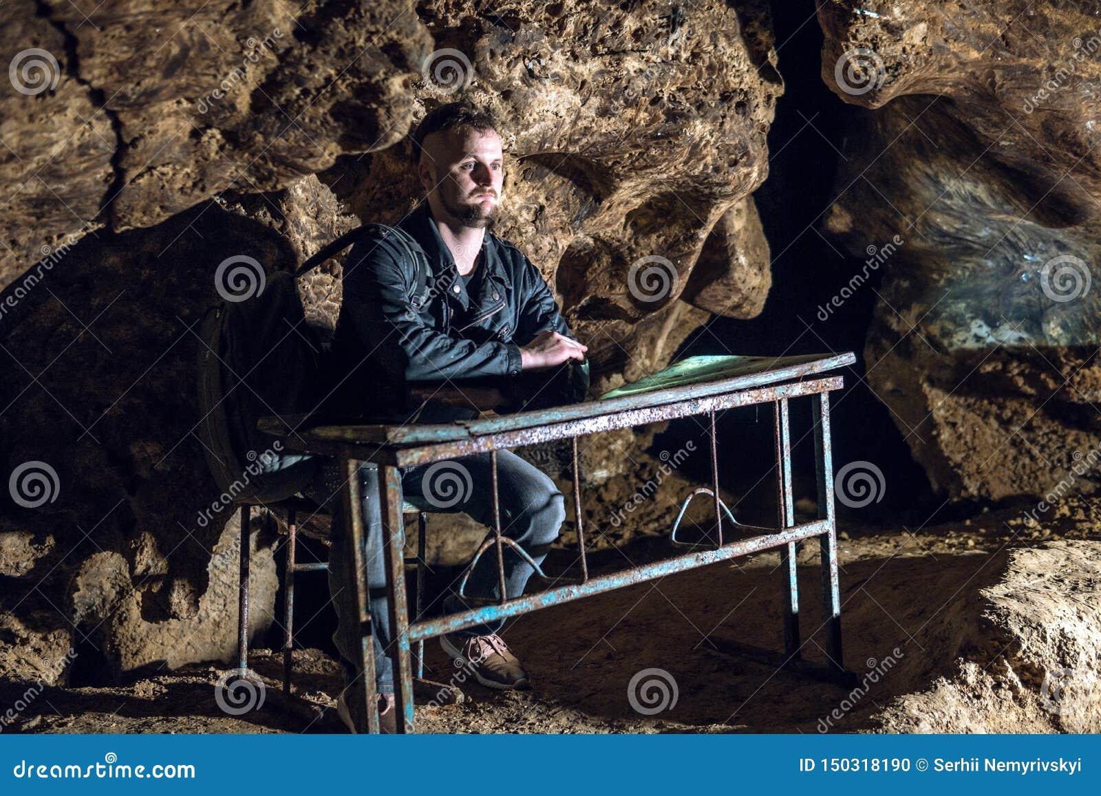 Ein Mann sitzt an einer Schulbank in einer dunklen Höhle Mist und Verwirrung auf dem Gesicht Lustige schlechte Bedingungen für St