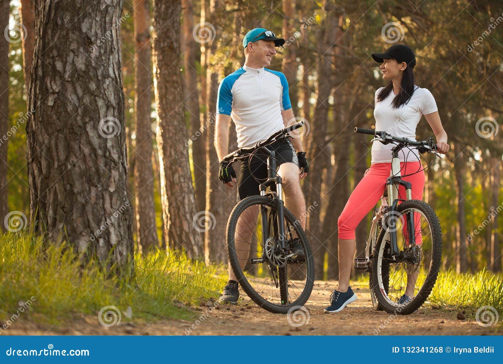 Ein Mann und eine Frau gehen Sie, im Wald radzufahren Fahrrad zur Natur