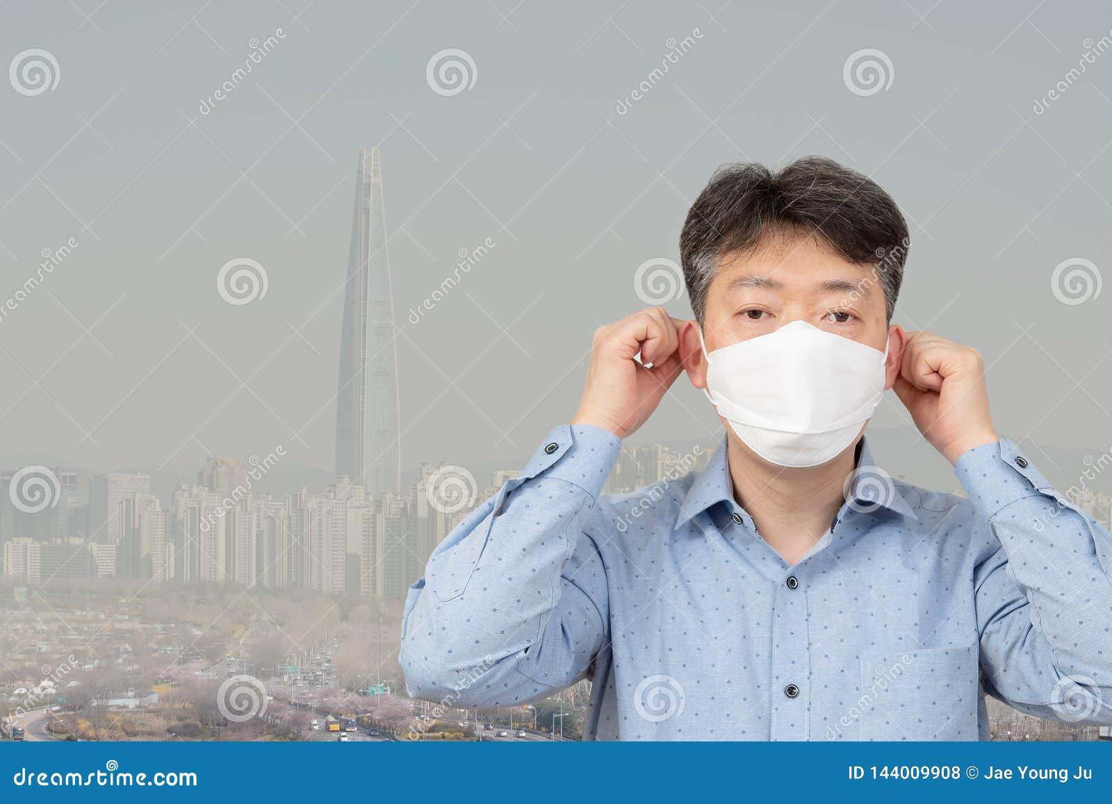 Ein Mann von mittlerem Alter, der voll eine Maske im Hintergrund einer Stadt des Feinstaubs trägt