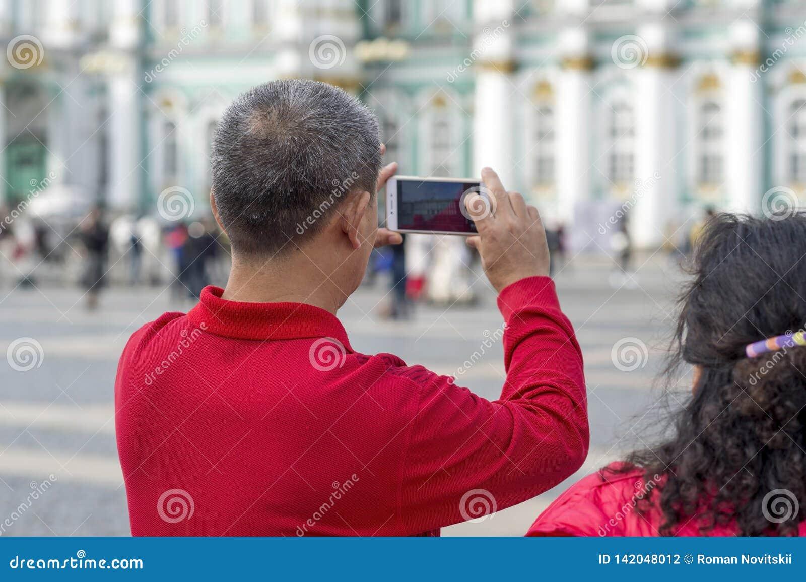 Ein Manntourist von asiatischen Auftrittphotographien auf einem Smartphone das Einsiedlereigebäude auf dem Palastquadrat von St P