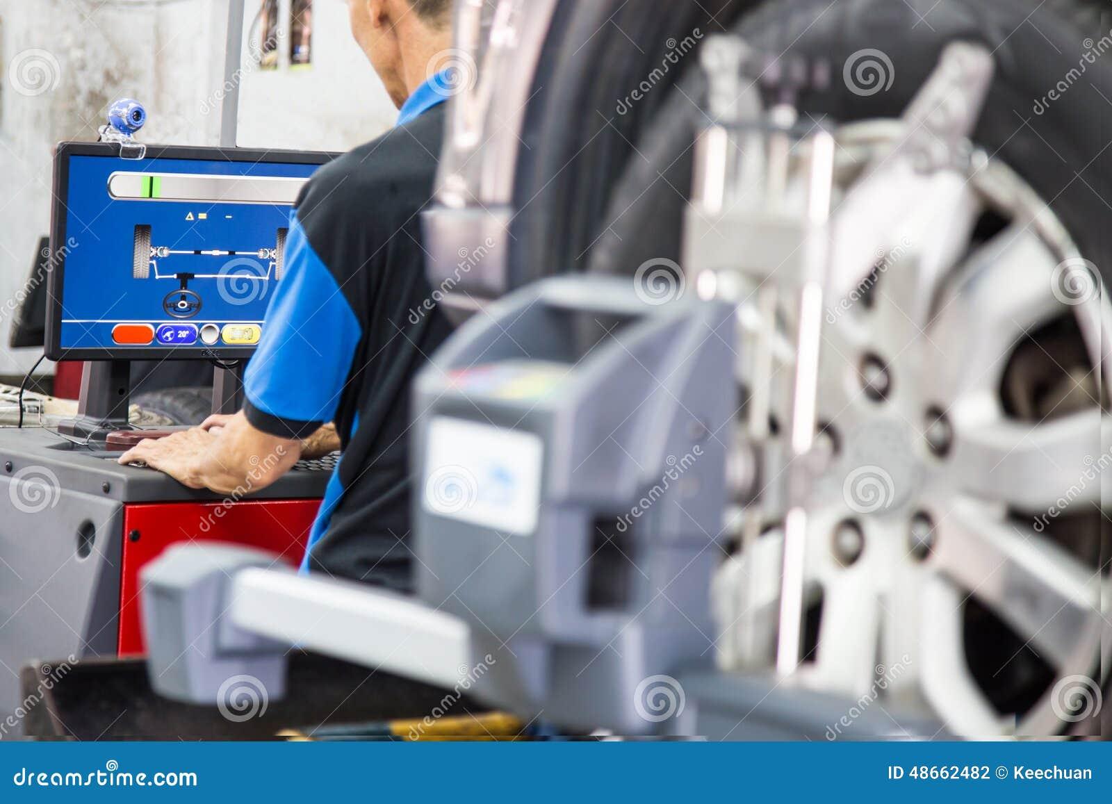 Ein Mechaniker, der den Computer benutzt, um den Radausrichtungsprozeß festzusetzen liest