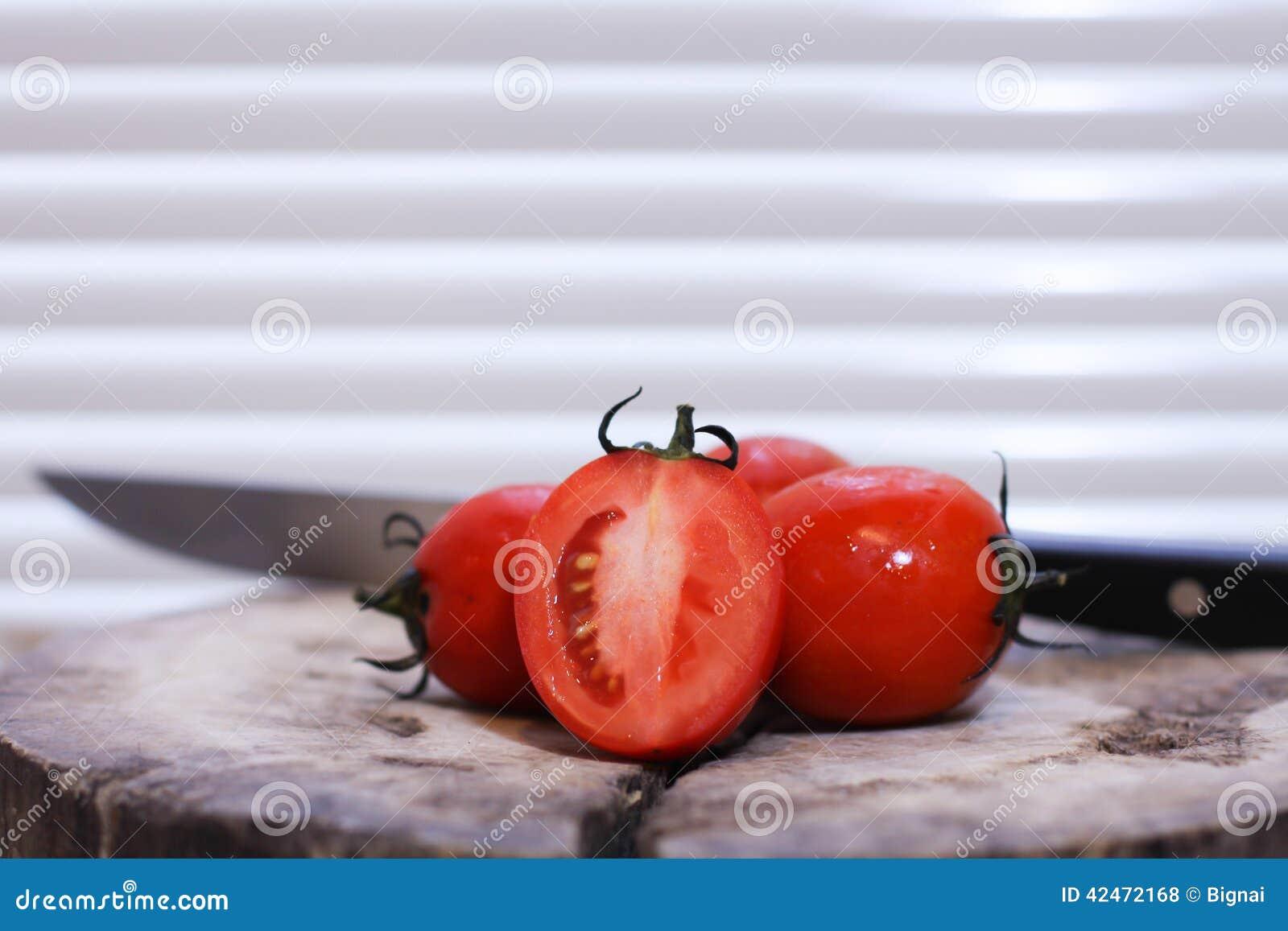 Ein Messer und ein tomatoeson ein hölzernes hackendes Brett