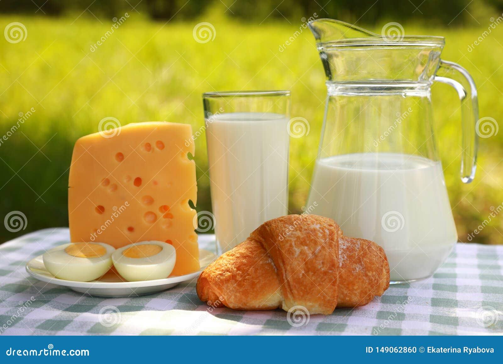 Ein Milchkrug, ein Glas Milch, ein Stück des Käses und des geschnittenen Eies auf einer Platte und ein Hörnchen auf einer grün-un
