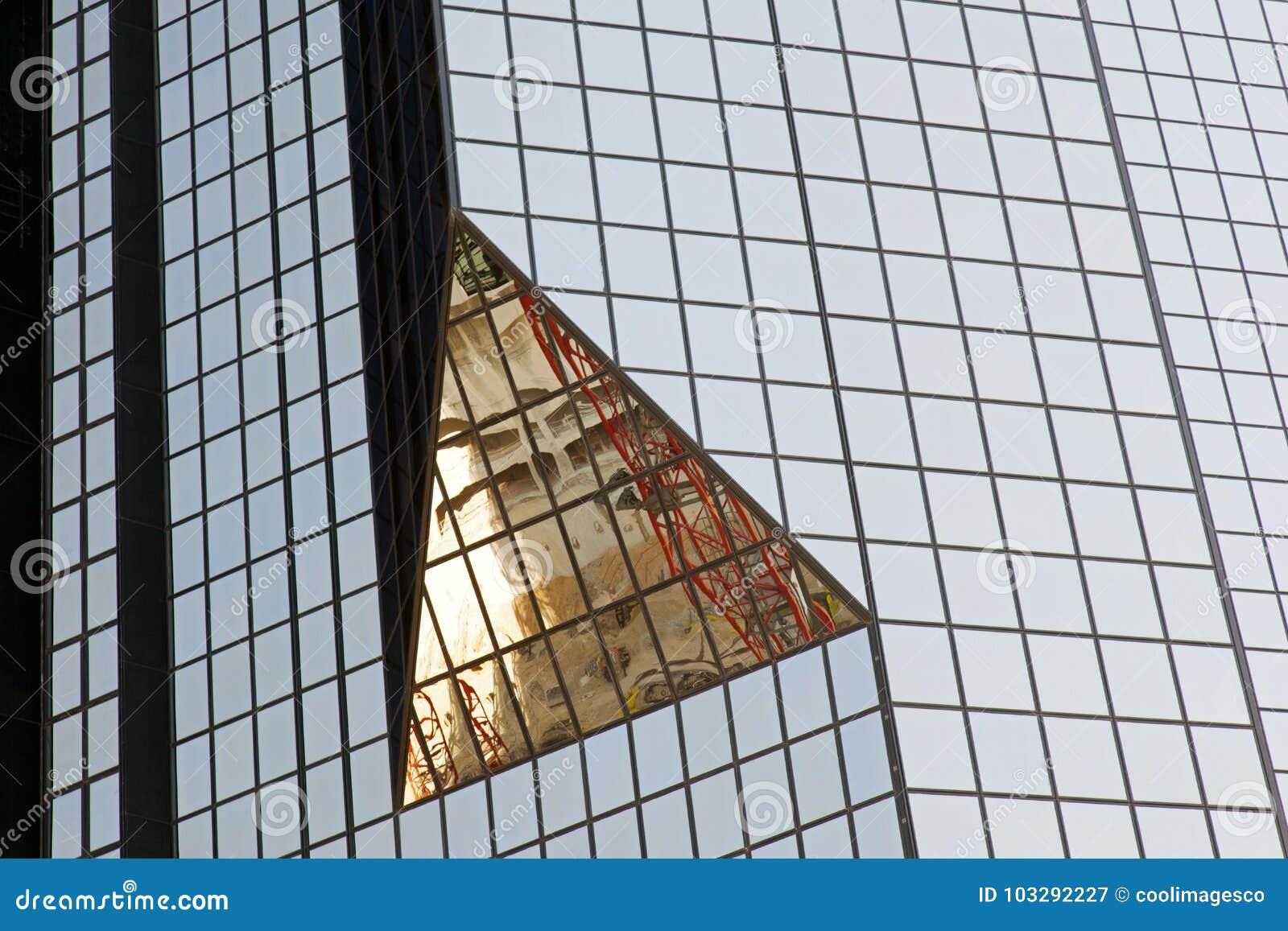 Ein modernes Glasgebäude mit geometrischen Winkeln und Reflexion