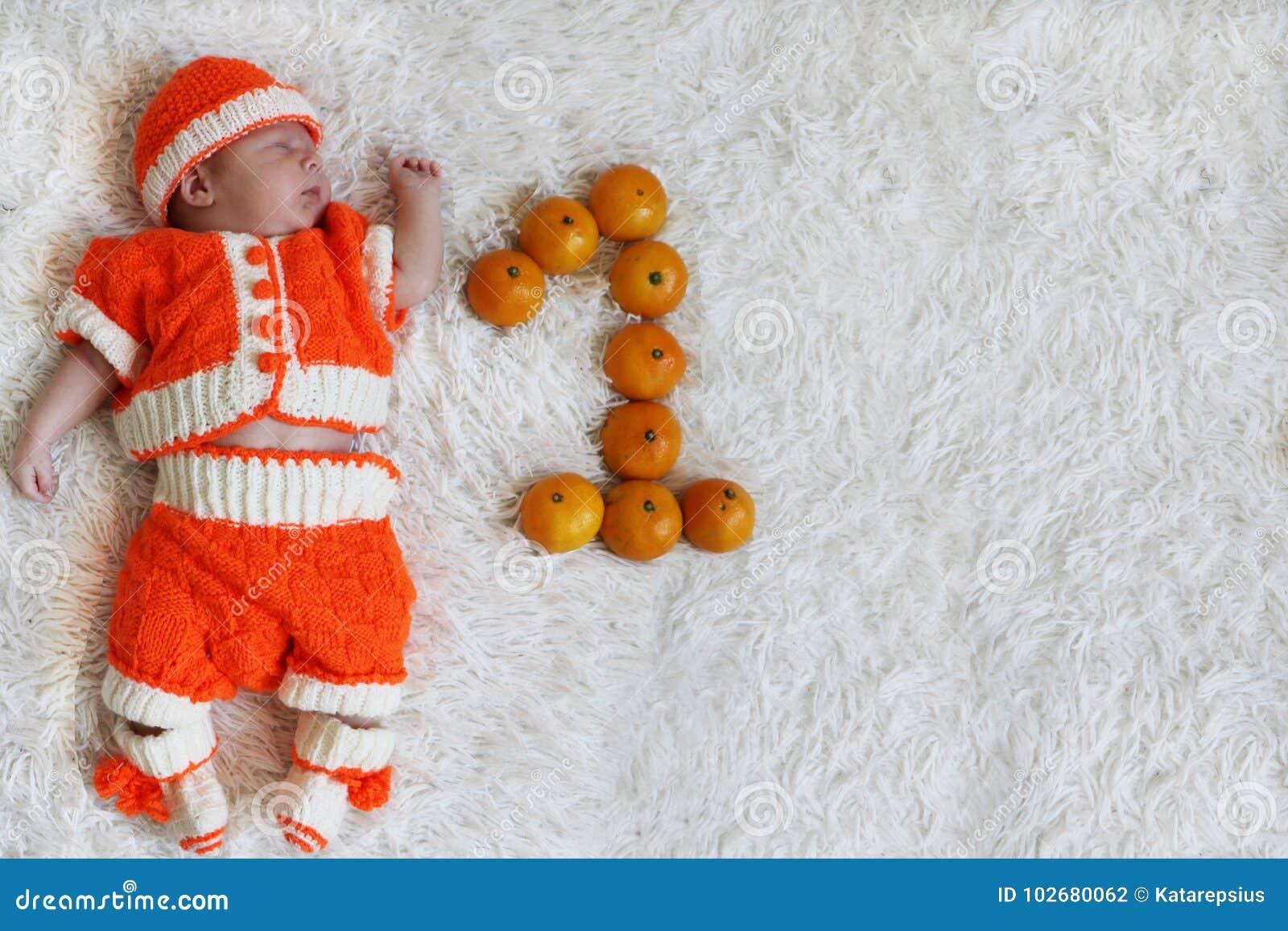 Ein Monatsschätzchen Schlafendes neugeborenes Baby ein Monat alt in der Orange