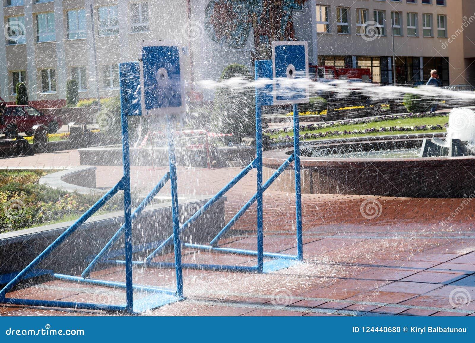 Ein nasser, starker Strom des Wassers spritzt und Trieb am Ziel, mit vielem Druck auf der Straße an der Anziehungskraft
