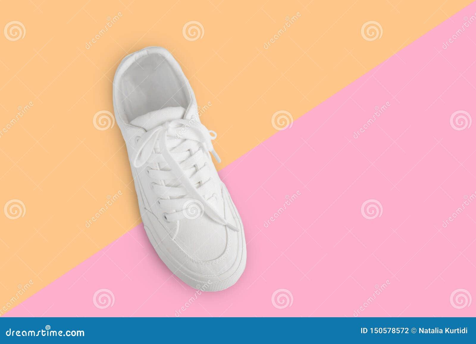 Ein neuer weißer weiblicher oder jugendlich Turnschuh lokalisiert auf gelb-rosa Hintergrund der Tendenz Weißer Textilturnschuh mi
