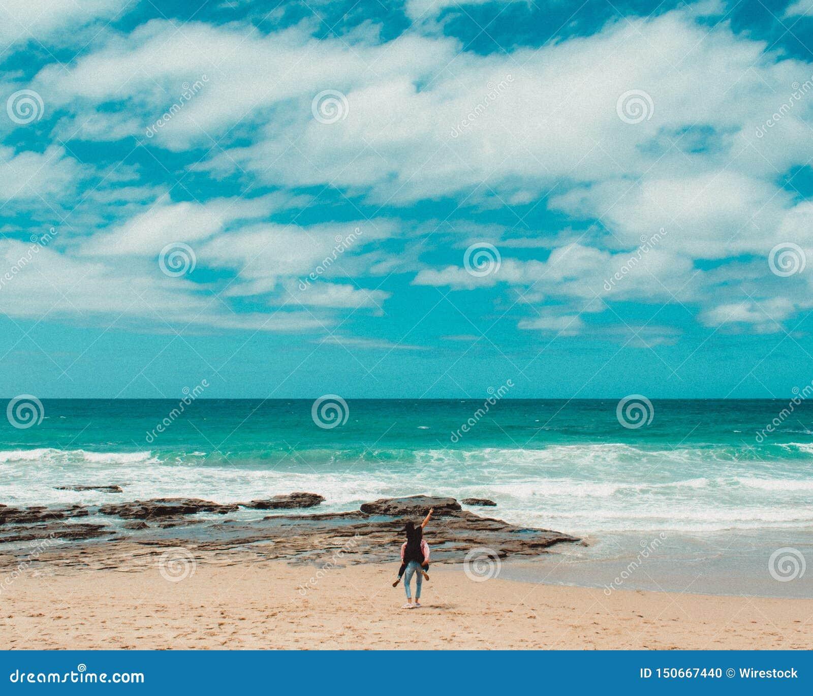 Ein Paar, das Spaß am schönen Strand mit blauem Himmel und Wolken und ein erstaunliches Meer hat