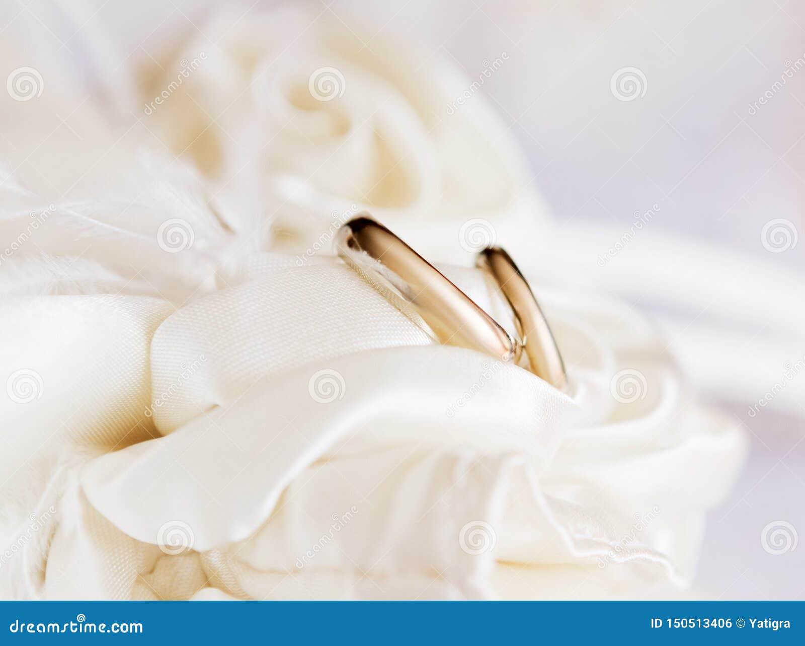 Ein Paar Heiratsgoldringe auf einer Auflage
