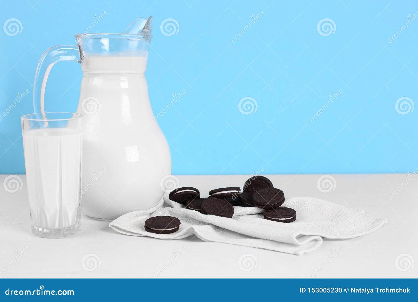 Ein Pitcher Milch und Glas Milch mit Plätzchen auf einem Holztisch auf einem blauen Hintergrund