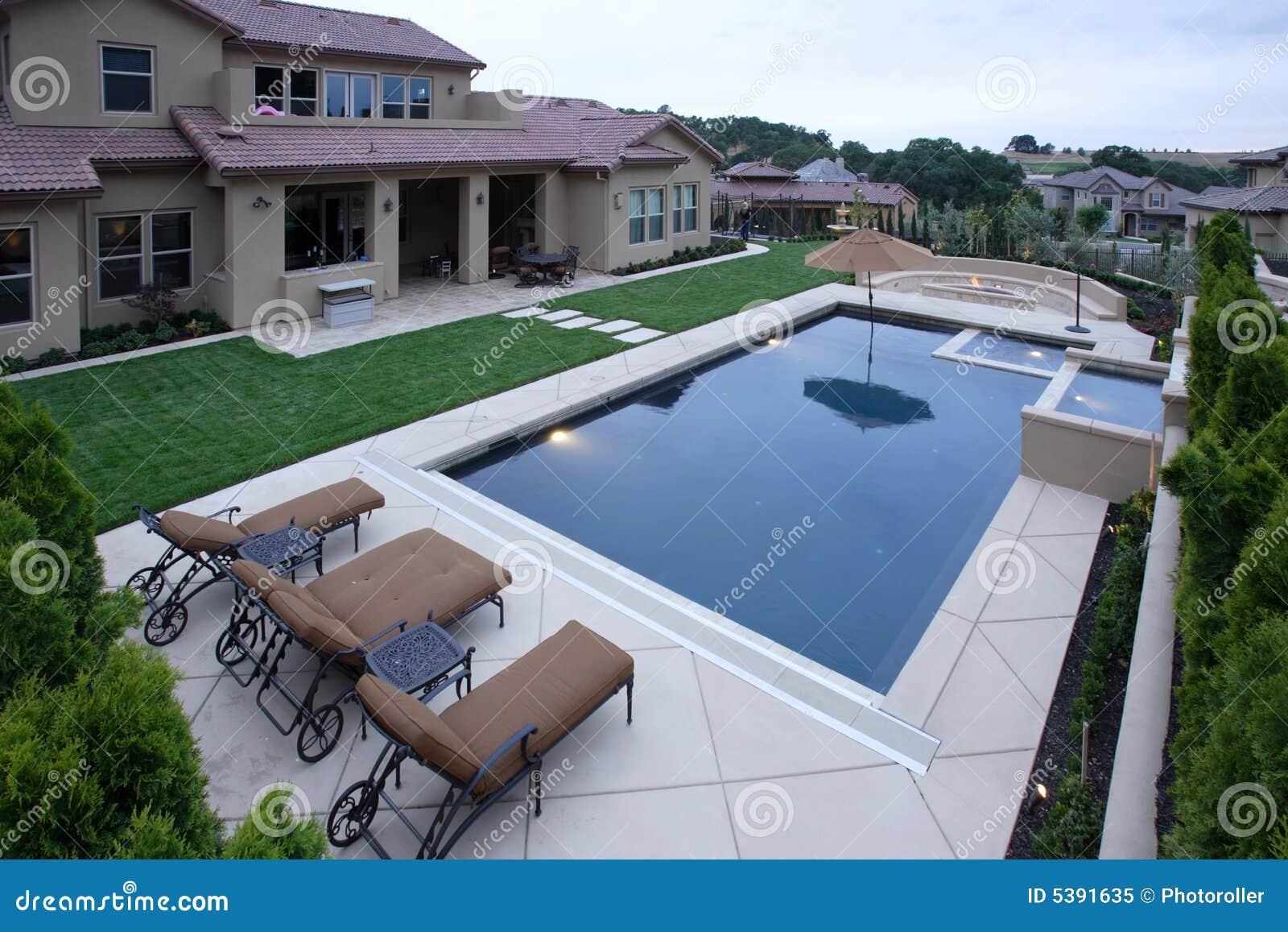 Luxus pool im garten wasserfall  Ein Pool Mit Einem Wasserfall In Einem Luxuxhinterhof Stockbild ...