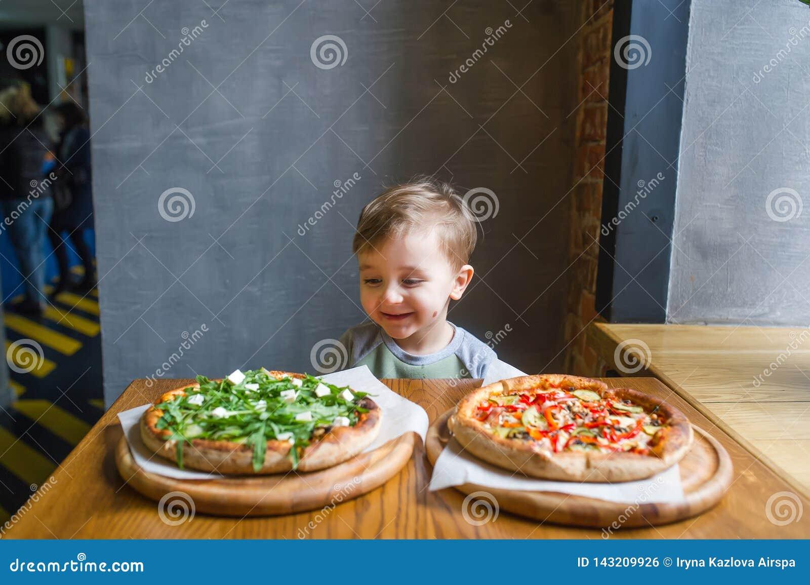 Ein Porträt des hübschen Kindes Pizza im angenehmen Café essend