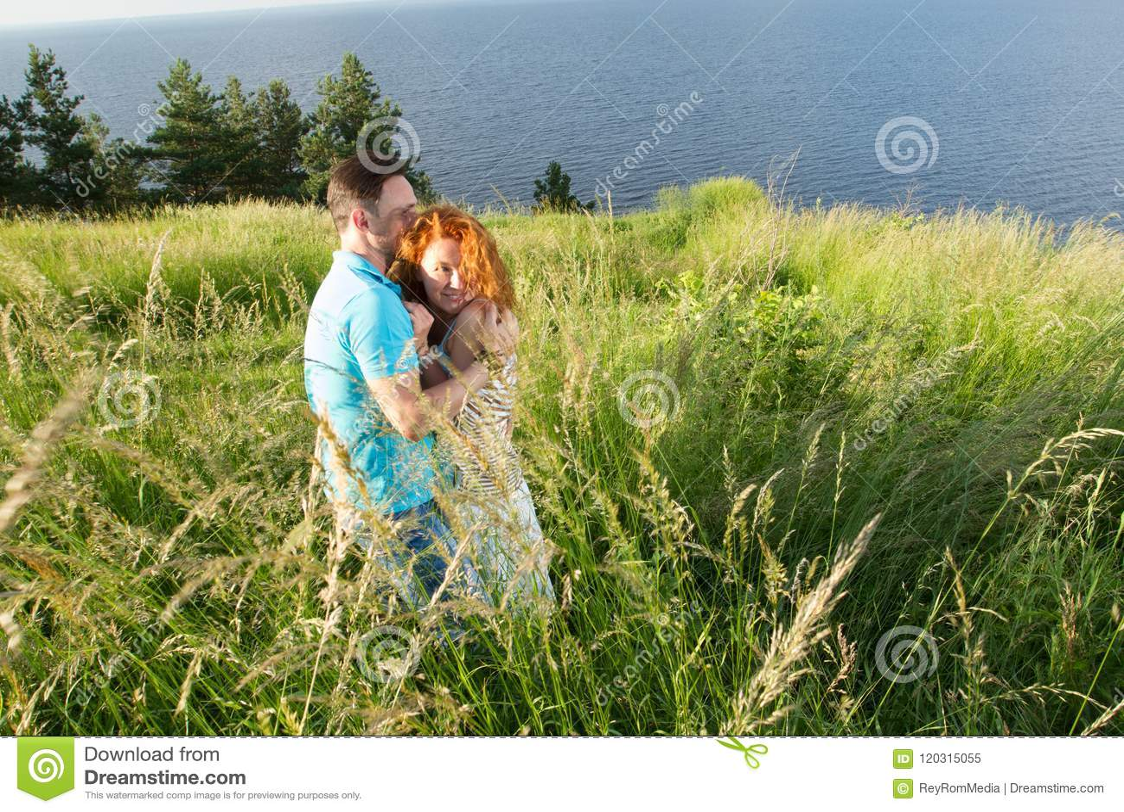 Ein Porträt von glücklichen schönen Paaren auf Natur mit großem See Junge Paare, die auf Bank von Fluss umarmen Mann, der rotes H