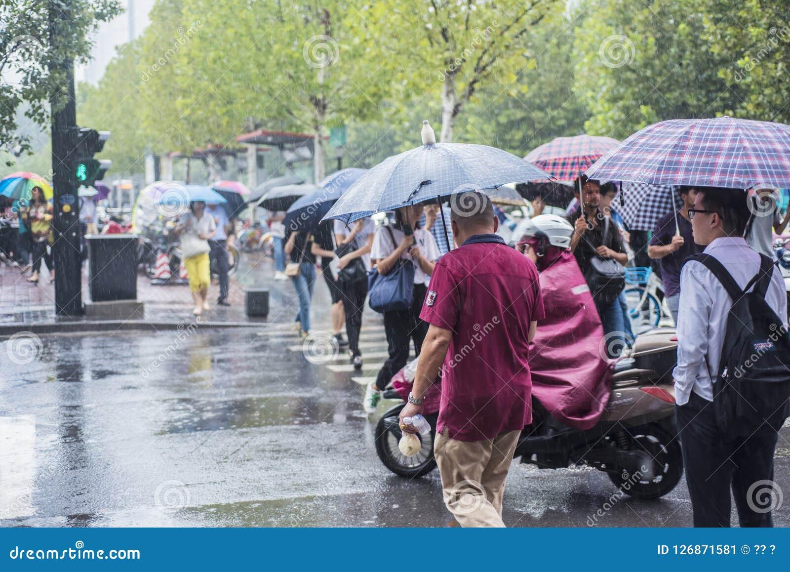 Ein Regen morgens, die Leute, die gehen zu arbeiten, kreuzte den Schnitt mit einem Regenschirm