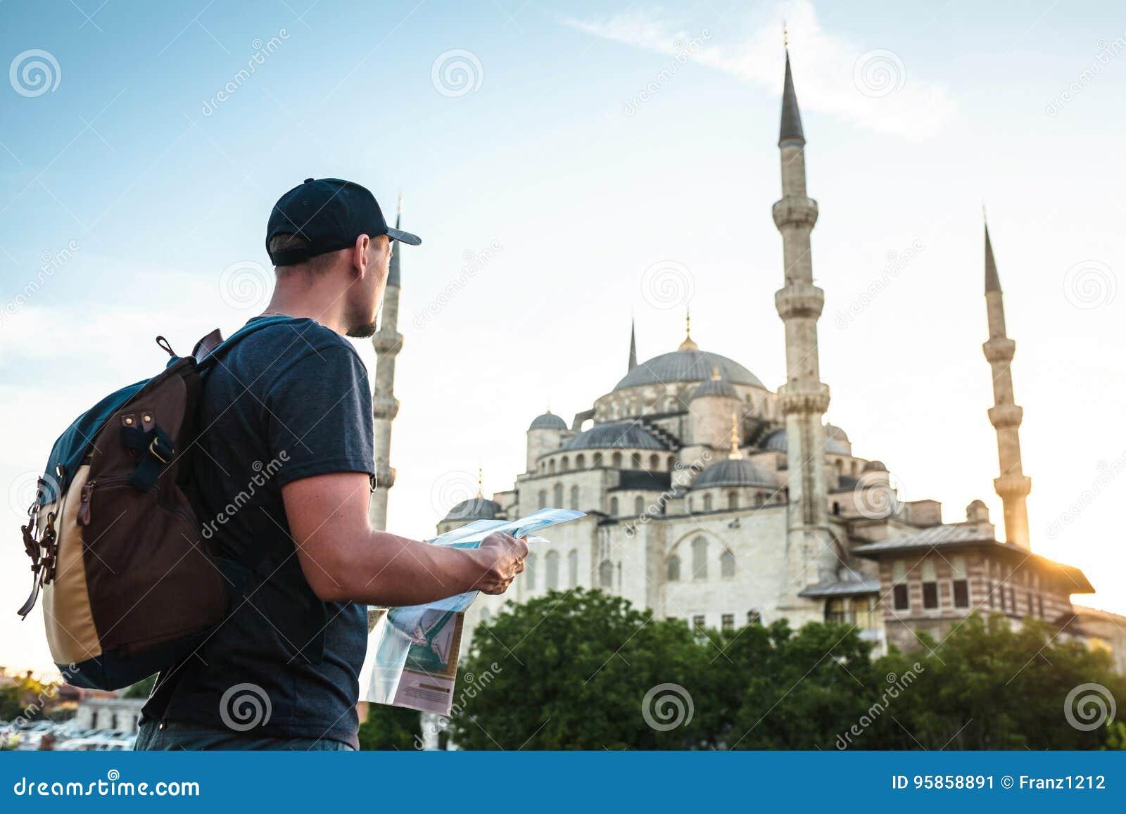 Ein Reisender in einer Baseballmütze mit einem Rucksack betrachtet die Karte nahe bei der blauen Moschee - der berühmte Anblick v