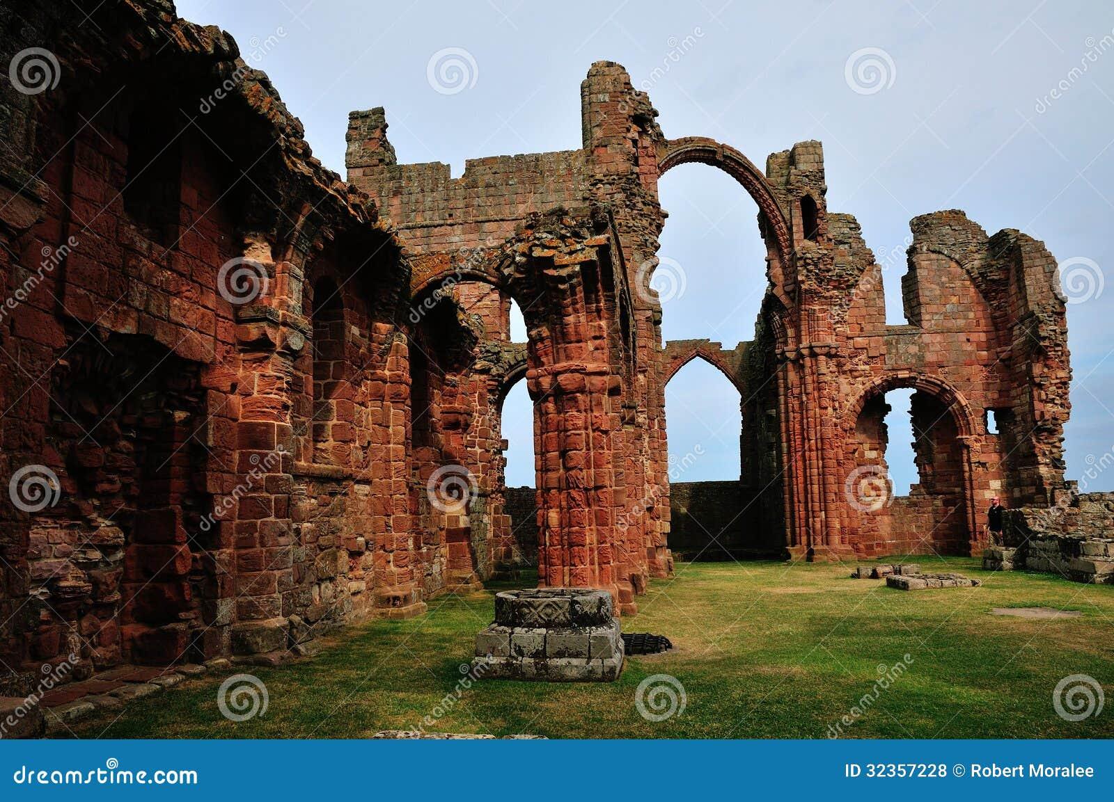 Ein ruiniertes Kloster, einen Regenbogen-Torbogen zeigend.