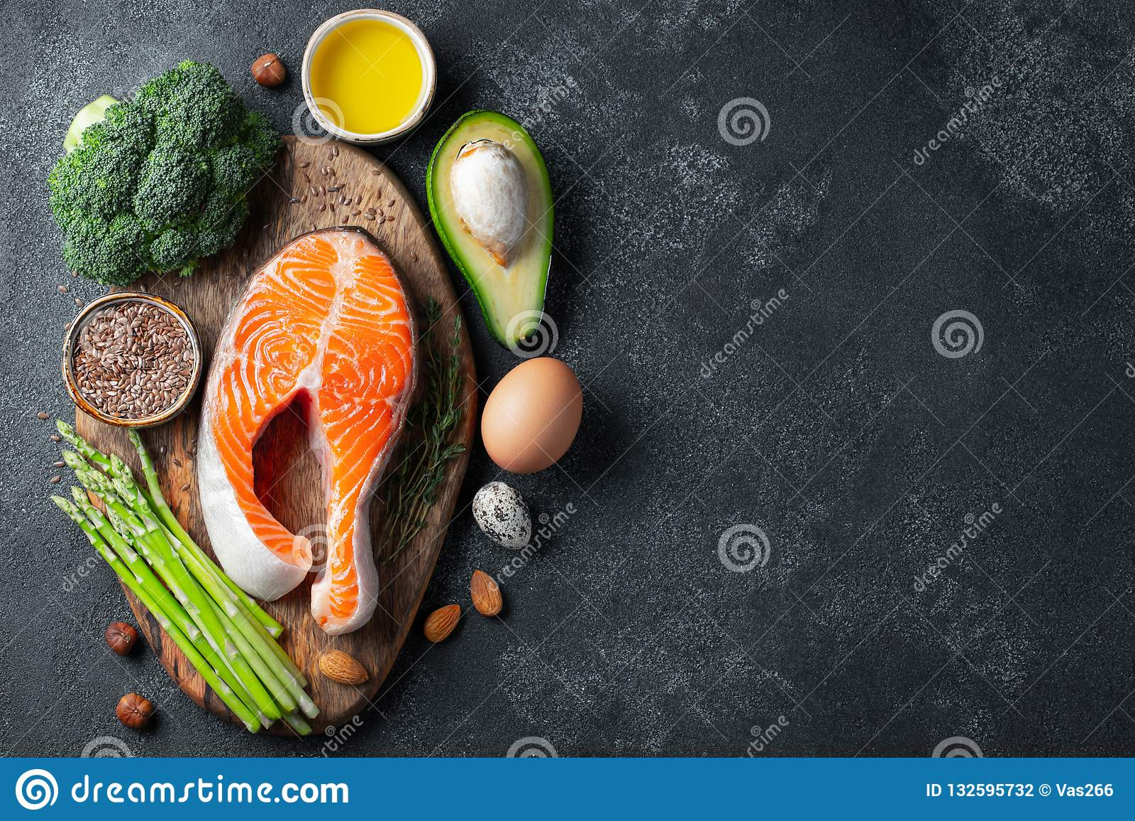 Ein Satz gesunde Nahrung für Keton-Diät auf einem dunklen Hintergrund Frisches rohes Lachssteak mit Leinsamen, Brokkoli, Avocado,