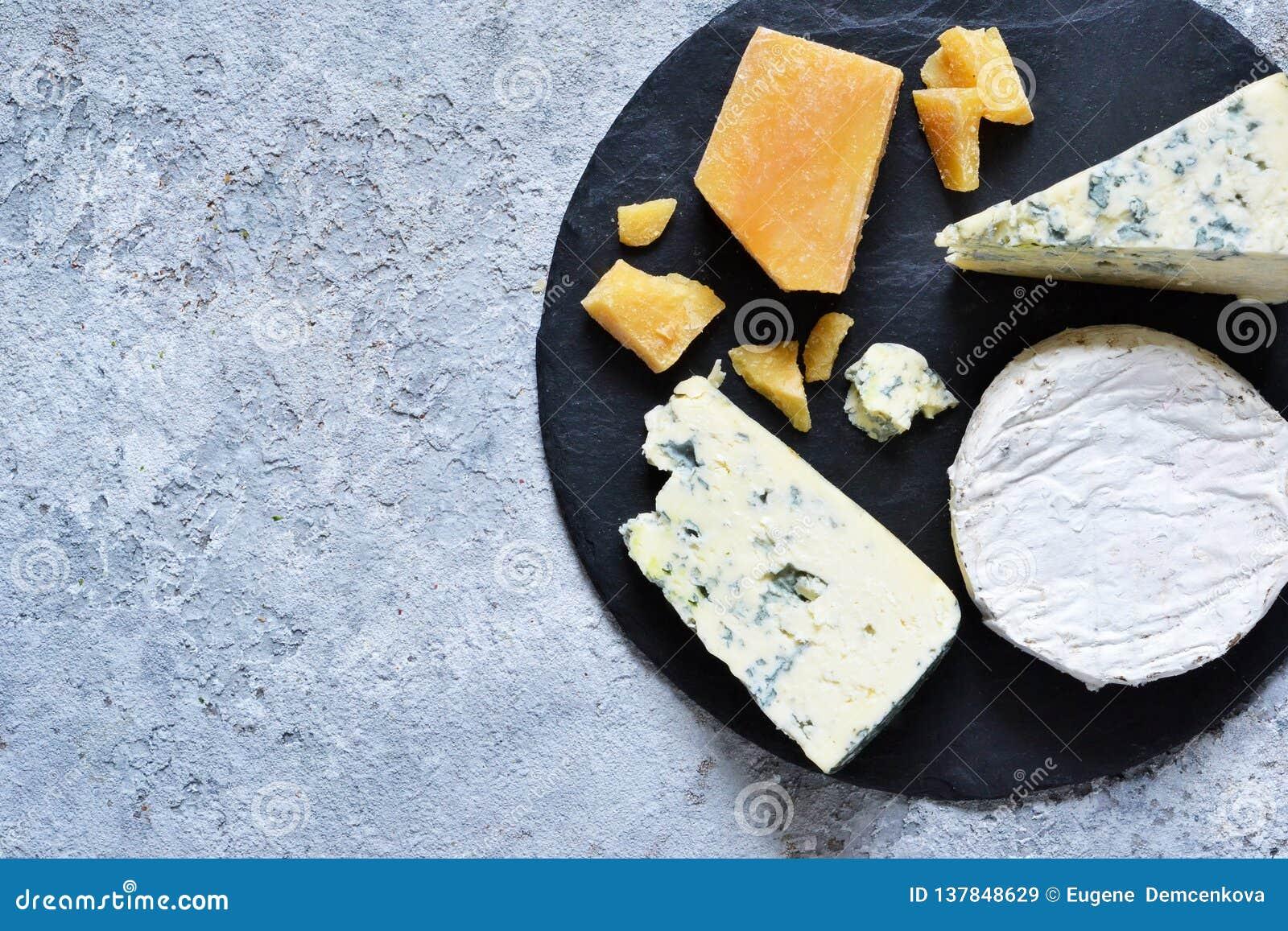 Ein Satz Käse: Briekäse, Blauschimmelkäse, Parmesankäse, Camembert auf einem Schieferbrett Platte mit Zartheit Ansicht von ob