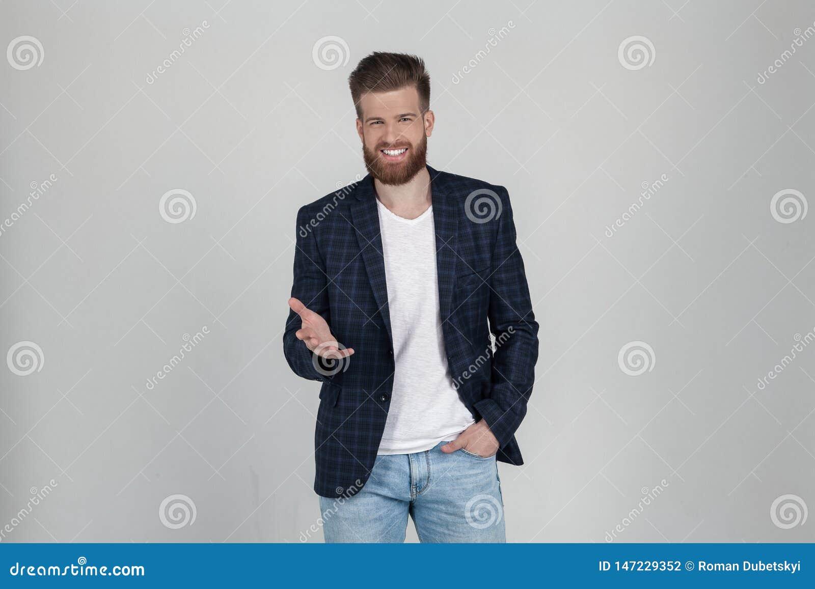 Ein sch?ner sexy b?rtiger Mann in einer Jacke hat positiven Ausdruck, Punkte mit dem Zeigefinger zur Kamera er steht vor