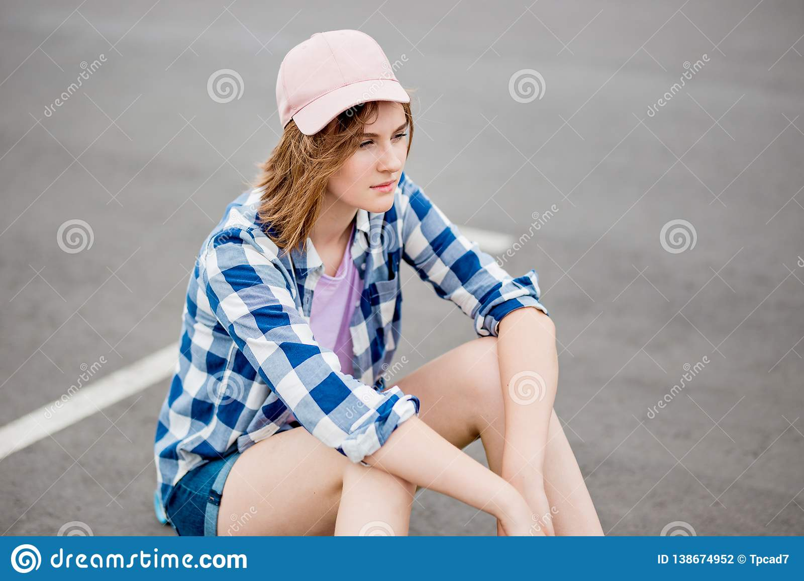 Ein schönes blondes Mädchen, das karierte Hemd-, Kappen- und Denimkurze hosen trägt, sitzt auf dem Parkplatz mit einem durchdacht