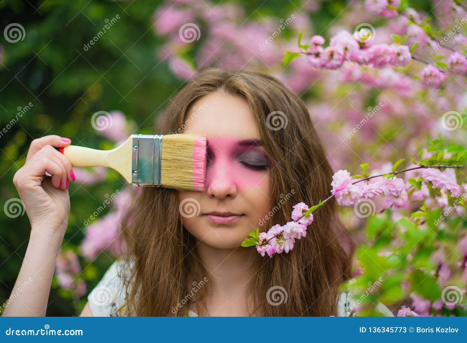 Ein schönes blondes Mädchen steht im Garten von einer blühenden rosa Kirschblüte mit ihren geschlossenen Augen und malt eine Bürs