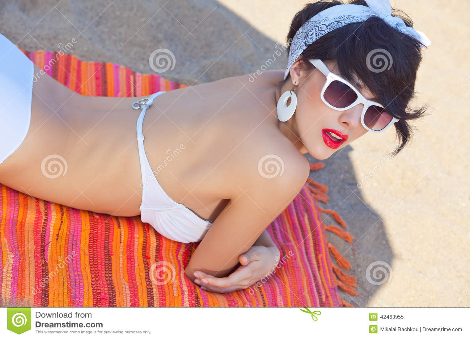 Ein schönes junges Mädchen im Retro Blick mit den roten Lippen in einem weißen Schalter