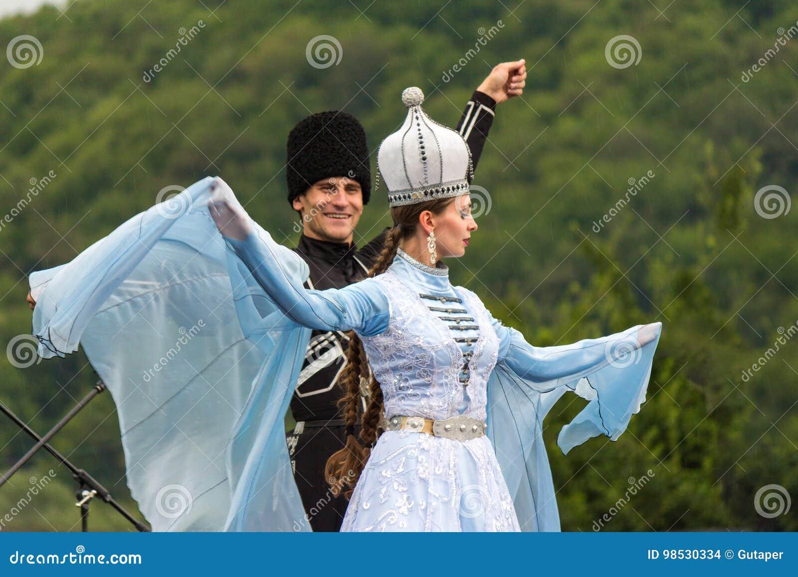 Ein schönes junges Mädchen und ein Kerl in traditionelle Circassian Kostüme tanzen am offenen Adyghe-Käsefestival in Adygea