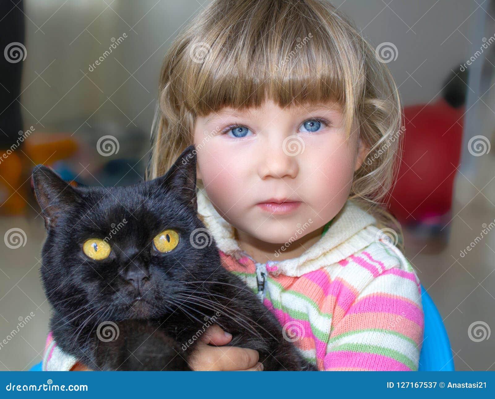 Ein schönes kleines Mädchen mit blauen Augen hält eine schwarze Katze Freundschaft mit Haustieren
