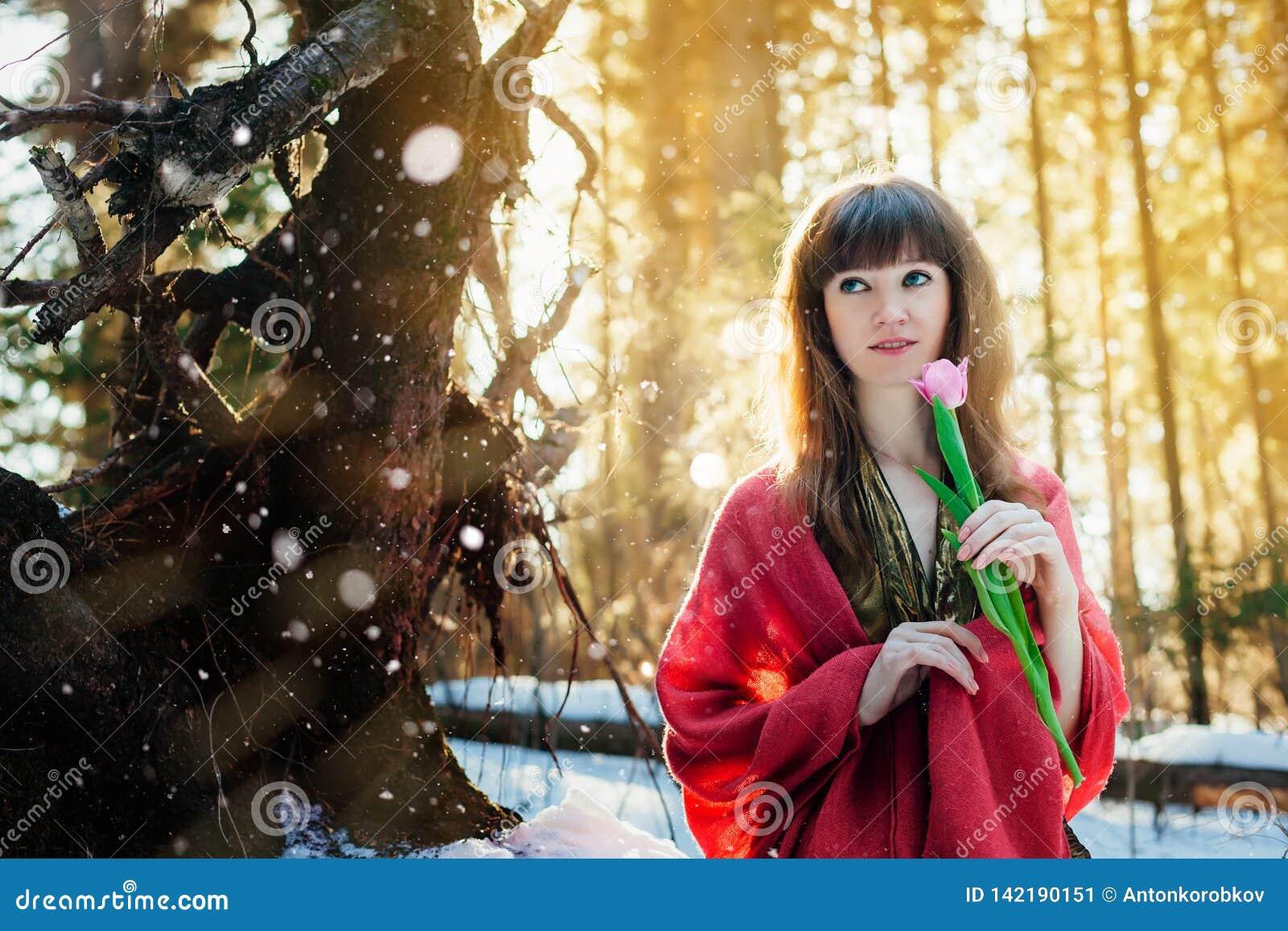 Ein schönes Mädchen in einem Goldkleid steht in einem sonnigen Wald des Frühlinges mit einer Tulpe in ihren Händen