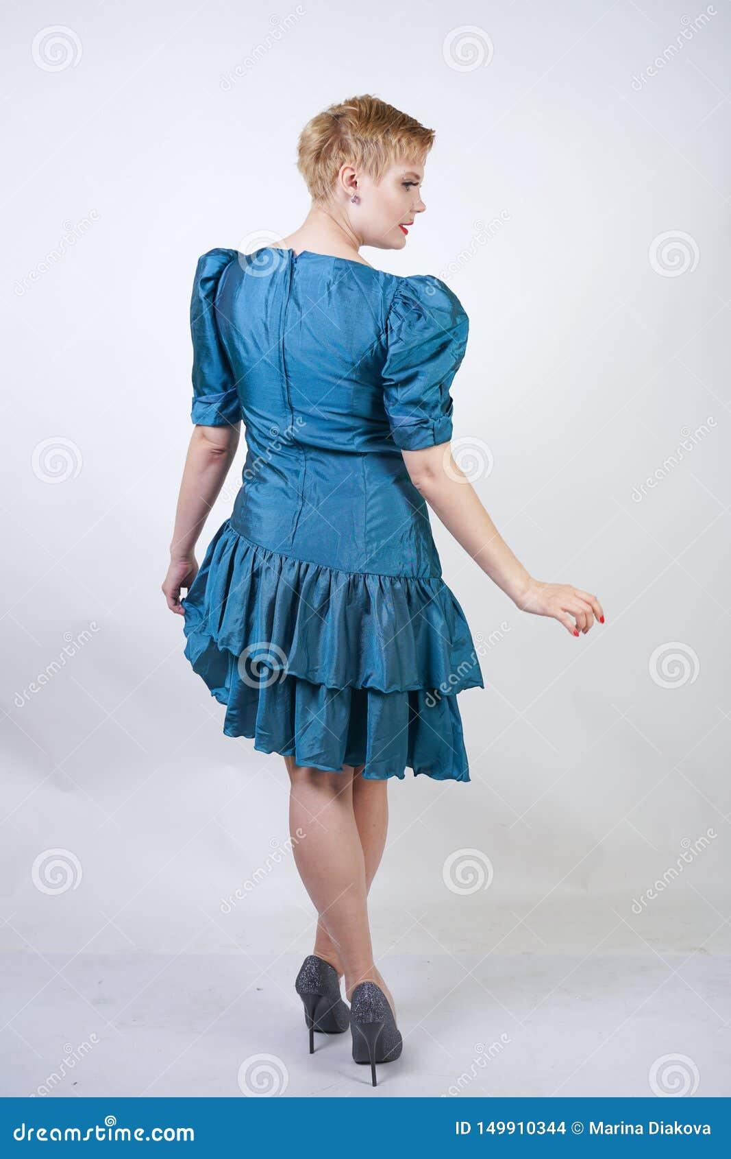 Ein schönes Mädchen mit einer Plusgrößenzahl gekleidet in einem netten Retro- Modekleid und -ständen auf einem weißen Hintergrund