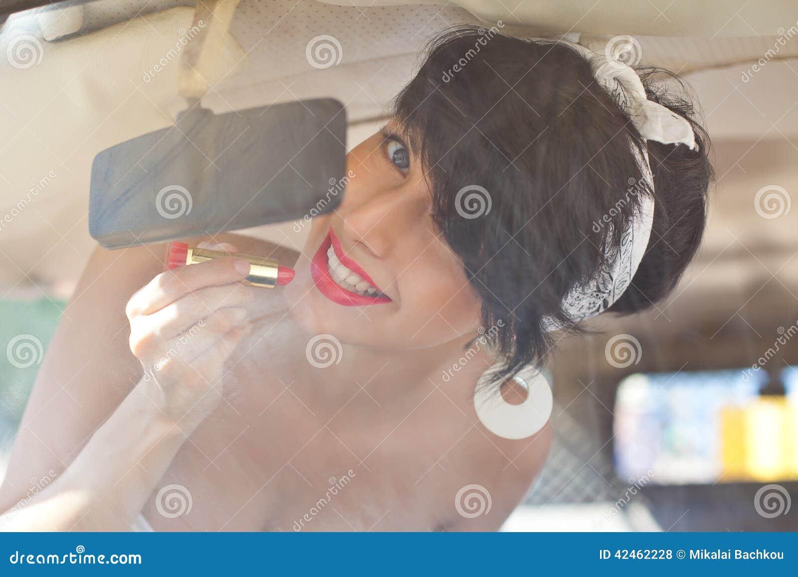 Ein schönes Retro-aussehendes Mädchen mit blauen Augen und rotem Lippenthrou