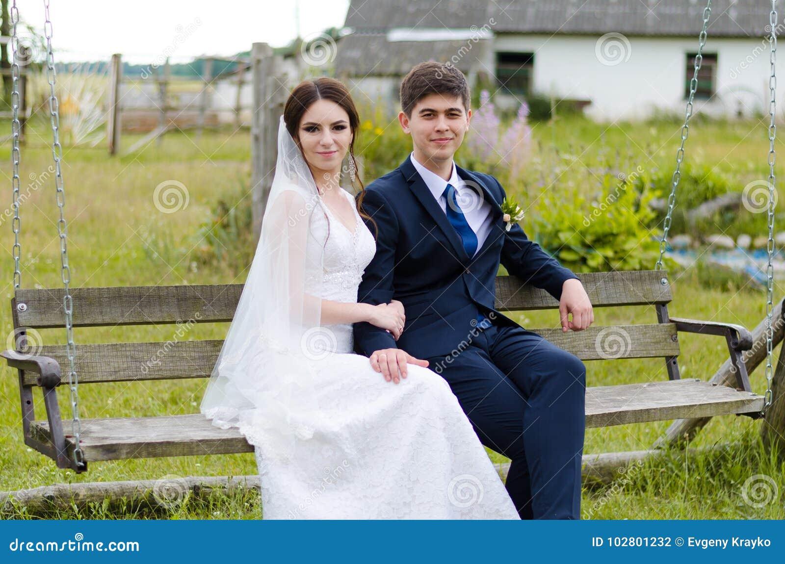 Ein schönes verheiratetes Paar in den Brautkleidern, werfend für ein Fotoschießen in einem belarussischen Dorf auf Grüner Hinterg