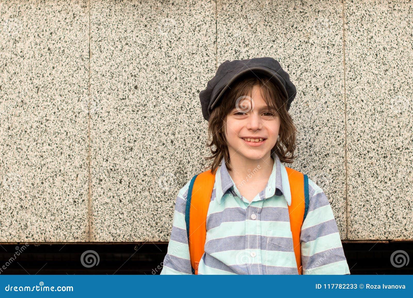 Ein Schüler blond, tragend in einem Hemd und in einer Kappe mit einem knapsacksta