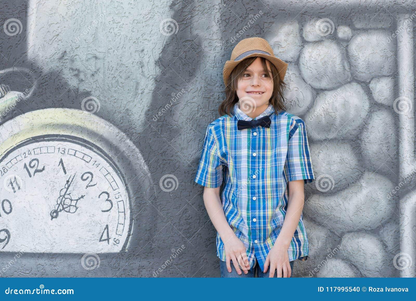 Ein Schüler in einem Hut und in einer Bindung - Schmetterling steht das te bereit