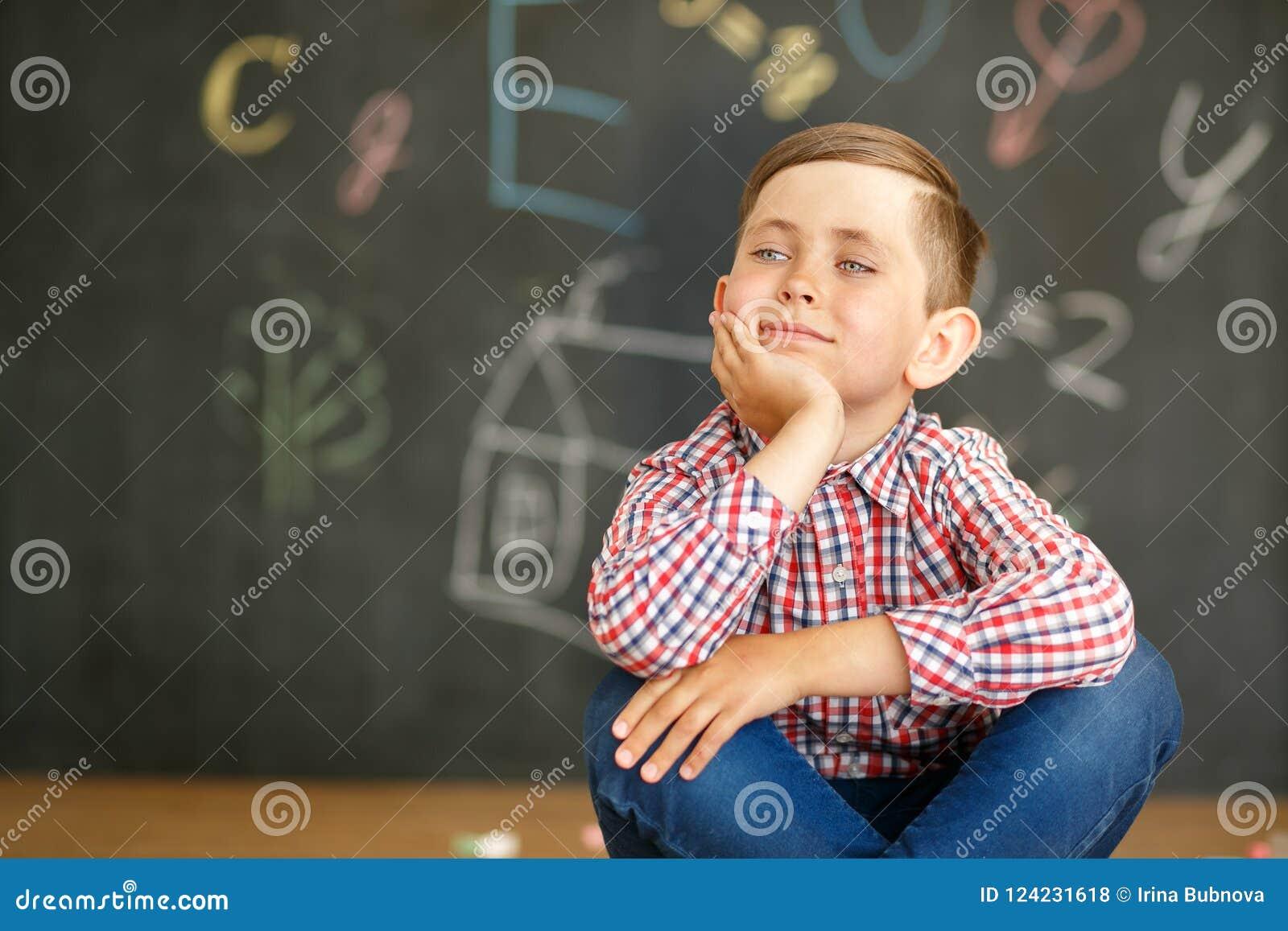 Ein Schüler sitzt auf dem Hintergrund einer Tafel, die mit Kreiden gemalt wird