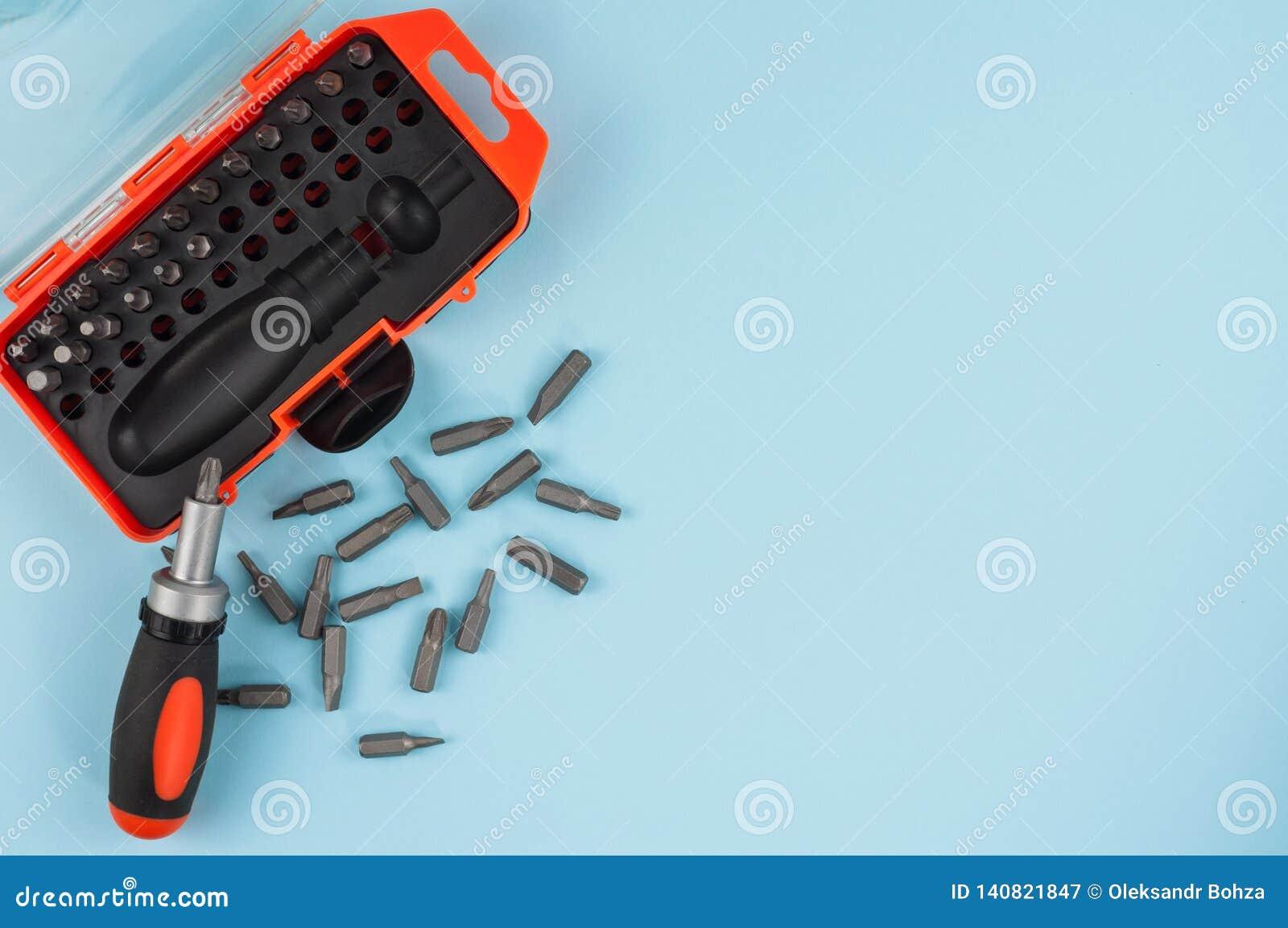 Ein Schraubenzieher mit Griff der schwarzen und orange Farbe nahe zerstreuten Metallstückchen und Plastikkasten für Stückchen