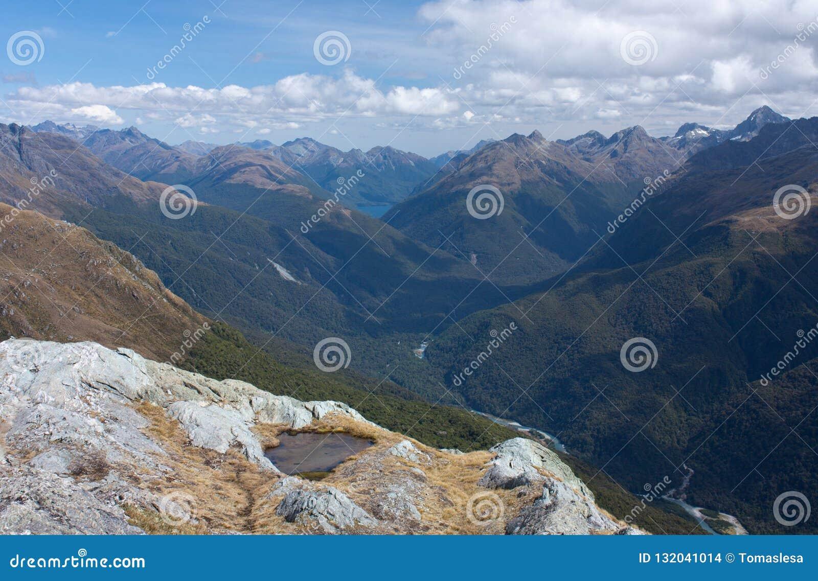 Ein See, ein Fluss und Berge, wie von der Spitze des konischen Hügels bei Harris Saddle am großen Weg Routeburn gesehen, neu