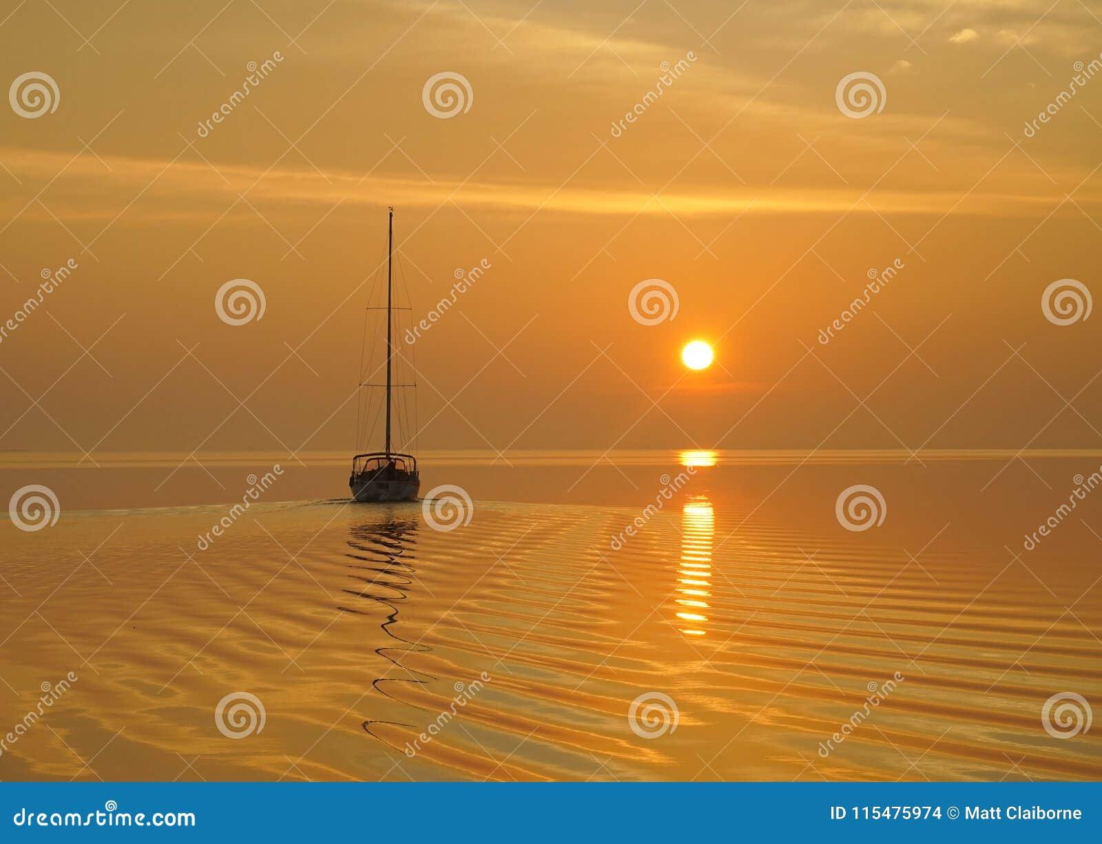 Ein Segelboot reist ein ruhiges Anchorage in helle gelbe sunris ab