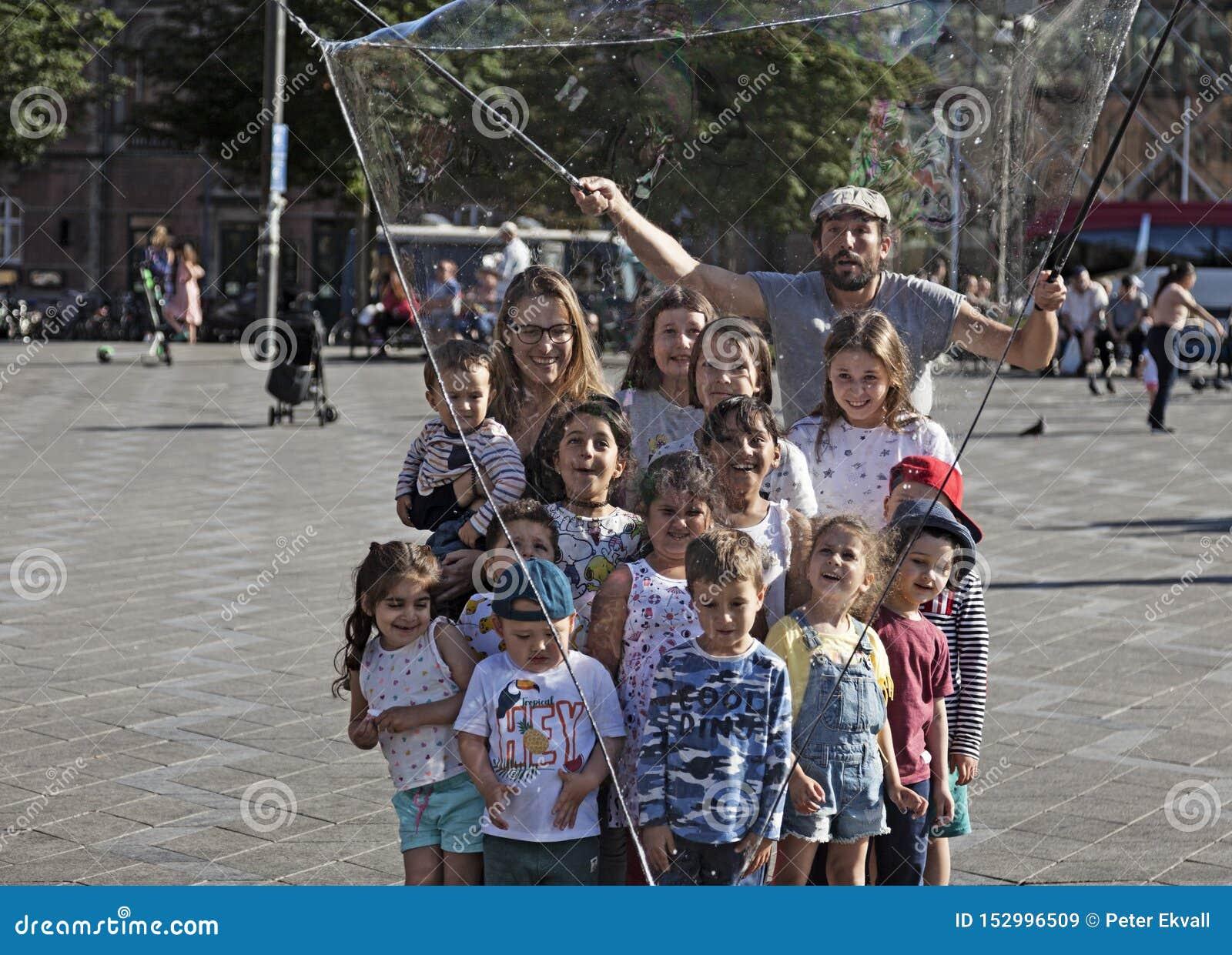 Ein Seifenblasekünstler lässt Kinder durch eine große Blase gefangen werden