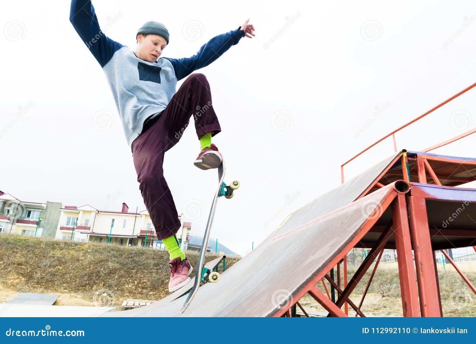 Ein Skateboardfahrerjugendlicher in einem Hut tut einen Trick mit einem Sprung auf der Rampe Ein Skateboardfahrer fliegt in die L