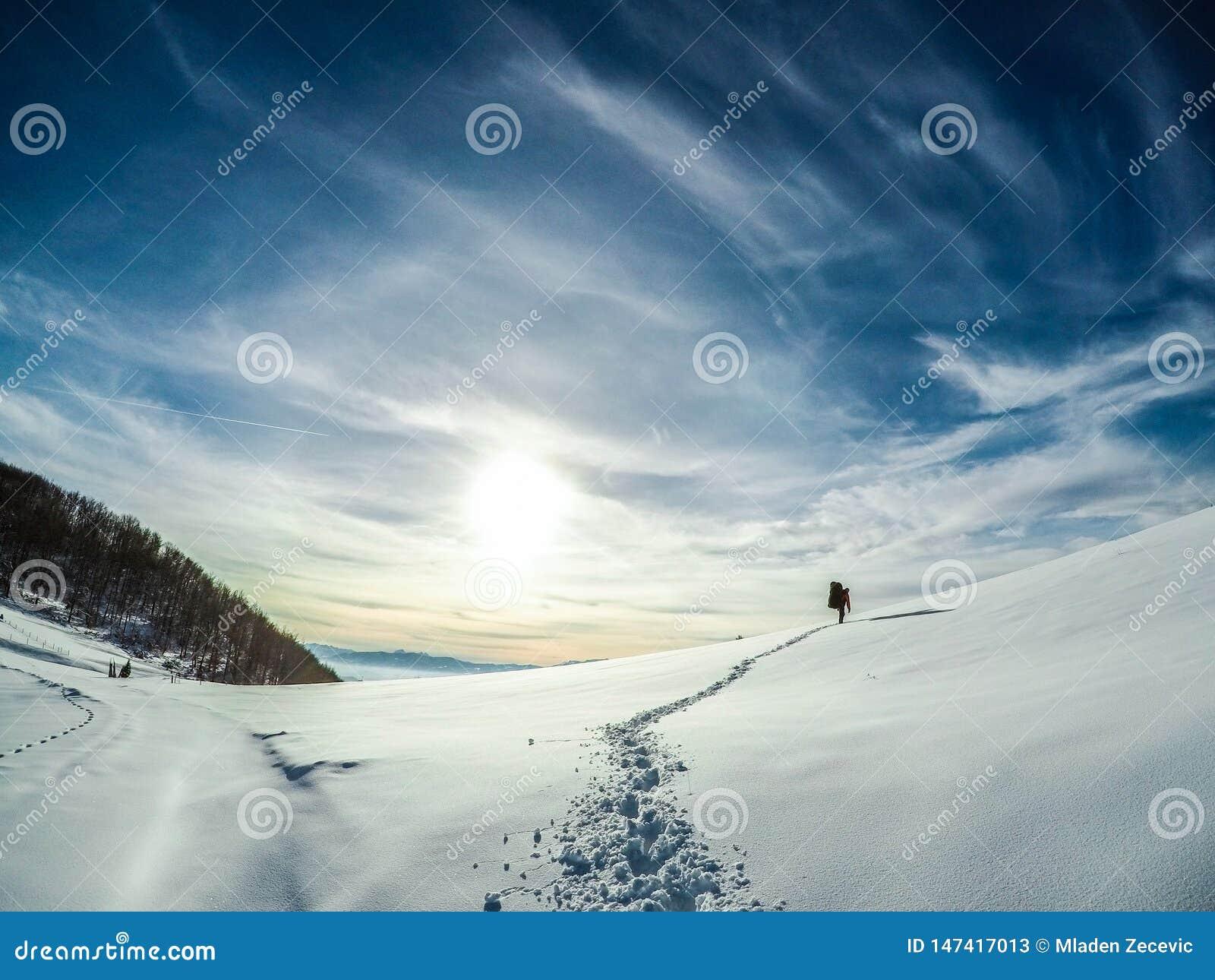 Ein snowboarde, das seine Weise herauf einen Berg macht, eine Fahrt zu machen